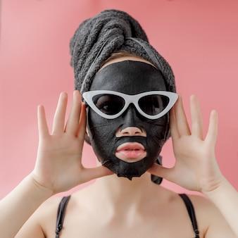 ピンクの背景に黒の化粧品ファブリックフェイシャルマスクを適用するメガネの若い女性。チャコール、スパエステ、スキンケア、美容のあるフェイスピーリングマスク。閉じる