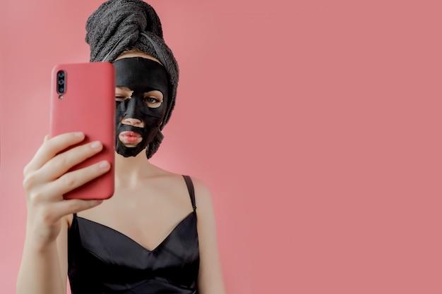 若い女性は、ピンクの背景の手に黒の化粧品ファブリックフェイシャルマスクと電話を適用します。チャコール、スパエステ、スキンケア、美容のあるフェイスピーリングマスク。閉じる