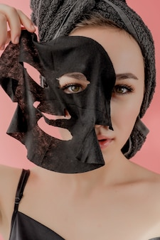 若い女性は、ピンクの背景に黒の化粧品ファブリックフェイシャルマスクを適用します。チャコール、スパエステ、スキンケア、美容のあるフェイスピーリングマスク。閉じる