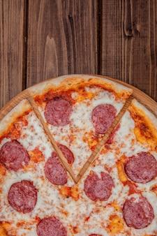 暗い木製の表面の上面にサラミとイタリアのペパロニのピザ。イタリアの伝統的な食べ物。人気の屋台料理