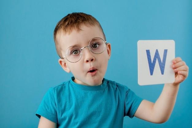 水色の壁に手紙とかわいい男の子。手紙を学ぶ子。アルファベット
