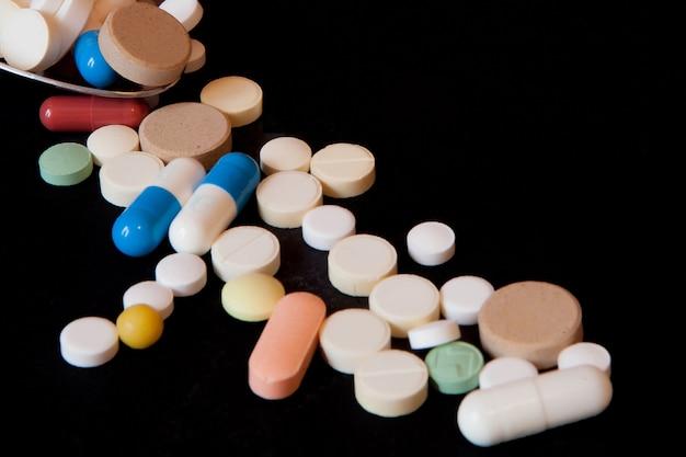 Аптека на черном столе. таблетки с ложкой. таблетки. медицина и здоровье. закройте капсулы. разные виды таблеток