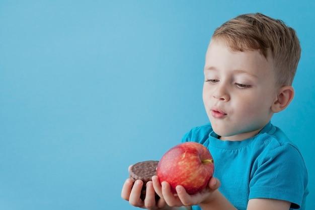 ジャンクフードを選択する幸せ、笑顔の少年の肖像画。健康的な食べ物と不健康な食べ物。健康的な食事と不健康な食事、ティーンエイジャーがクッキーまたはリンゴを選ぶ