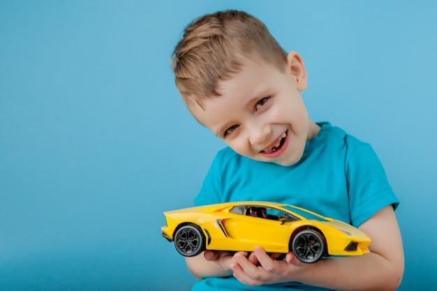 Маленький мальчик играет с большой желтый автомобиль на синей стене
