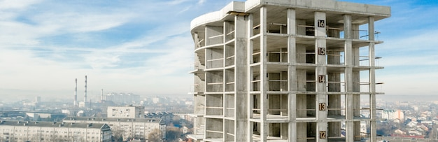 都市で建設中の背の高いマンションのコンクリートフレームの空撮のパノラマ