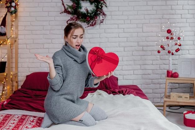 Портрет девушки в сером свитере с красной подарочной коробкой в форме сердца, сидящей в квартире, концепция дня святого валентина, копия места