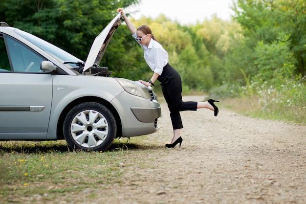 車が故障した後、道端で若い女性彼女はボンネットを開けて損傷を確認しました