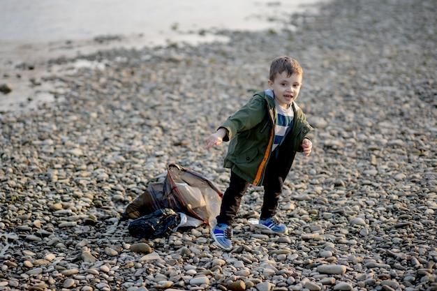 Маленький мальчик собирает мусор и пластиковые бутылки на пляже, чтобы выбросить в мусор