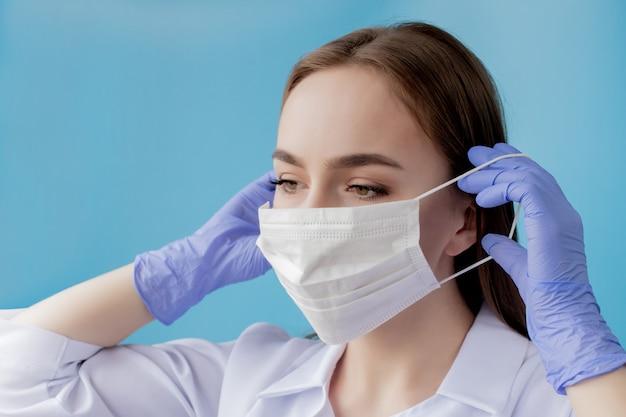 医師看護師が外科医のマスクの後ろに笑っています。青の若い白人女性モデルのポートレート、クローズアップ