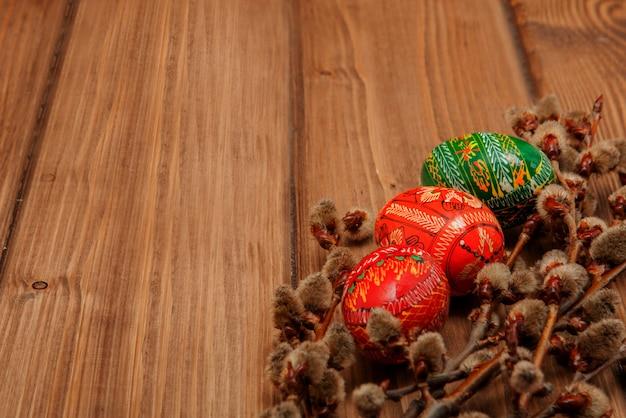 ピサンカのある静物、飾られたイースターエッグ、黒い木製の背景、上面図、コピー領域の乾燥した柳の枝