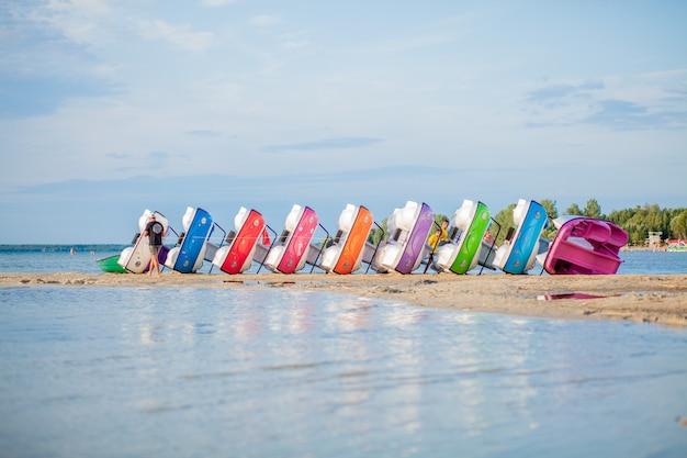 湖に積み上げられたカタマラン。湖のビーチで明るくカラフルなペダルボート