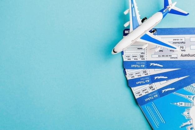 青色の背景にパスポート、飛行機、航空券。旅行の概念、コピースペース
