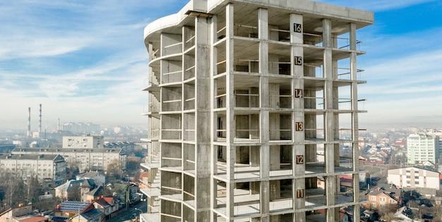 都市で建設中の高層マンションのコンクリートフレームの空撮のパノラマ