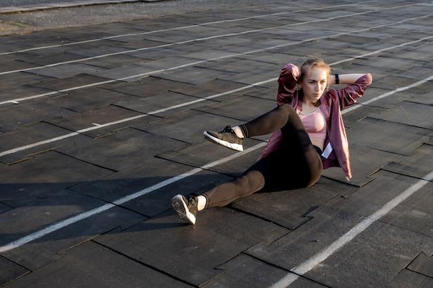Спортсменка, подготовка ноги для кардио тренировки. фитнес бегун делает разминку. женщина бегун разминки на открытом воздухе. спортсмен растягивается и разминается на беговой дорожке на стадионе