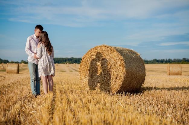 わら、ロマンチックな人々、美しい風景、夏のシーズンに幸せな若いカップル