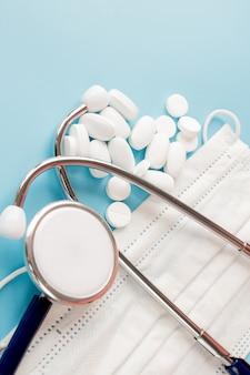 Композиция с медицинским стетоскопом, одноразовые маски для лица таблетки на синем фоне. вид сверху. бесплатная копия пространства.