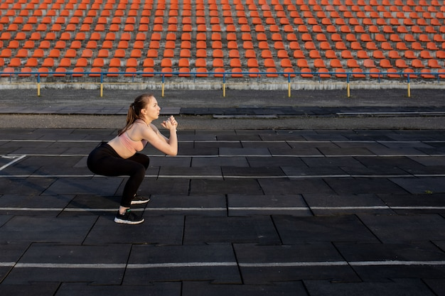 有酸素運動の脚を準備する女性アスリート。ウォーミングアップルーチンを行うフィットネスランナー。女性ランナーは屋外をウォームアップします。アスリートは、スタジアムのランニングトラックでストレッチしてウォーミングアップ