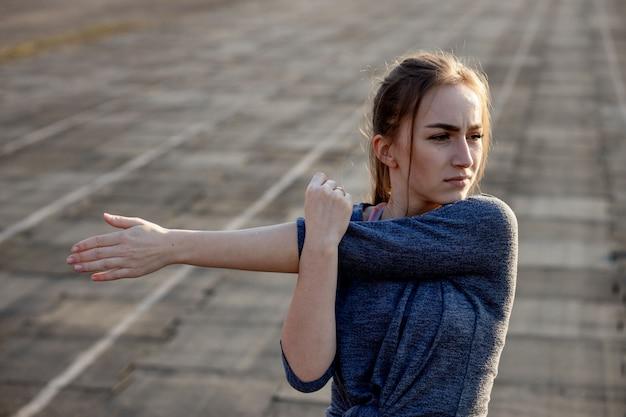 若い女性は夏にスタジアムでトレーニングします。スポーツウーマン、ストレッチ、外で運動する前にウォーミングアップ。健康的な生活様式