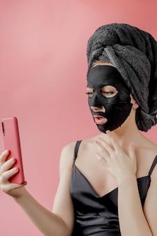 Молодая женщина применять черные косметические ткани маска для лица и телефон в руках на розовом фоне. маска-пилинг для лица с древесным углем, спа-салон красоты, уход за кожей, косметология. закрыть