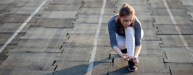 スタジアムのランニングトラックでスニーカーをひもで締める女性ランナー。健康的な生活様式
