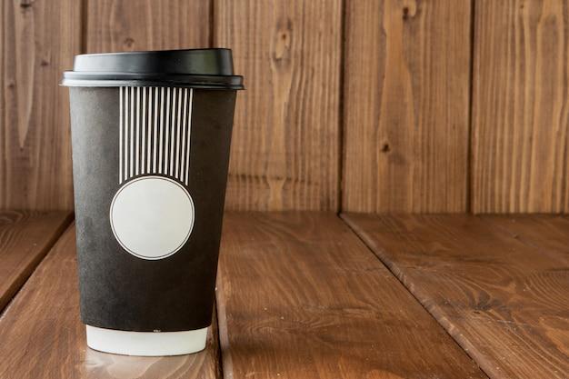 Вынос кофе в термо чашке на деревянном фоне