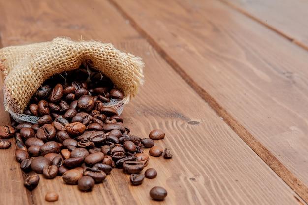 Свежий жареный кофе в зернах, выпадая мешок на деревянные поверхности.