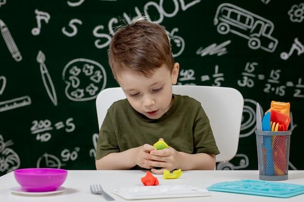 背景に黒板とテーブルの上の粘土からかわいい男の子金型。学校の準備ができています。ホームスクーリング。学校に戻る