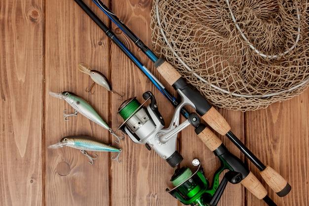 釣り道具-釣り糸、フック、木製の背景にルアー