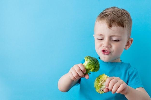 Маленький ребенок держит брокколи в его руках на синем фоне. веганская и здоровая концепция