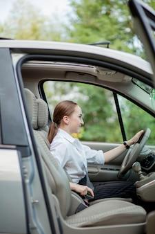 女性の手が車のシートベルトを締めます。運転する前に車内に座っている間にシートベルトを閉め、安全な旅をしてください。女性ドライバーのクローズアップショットは、シートベルトを締めます