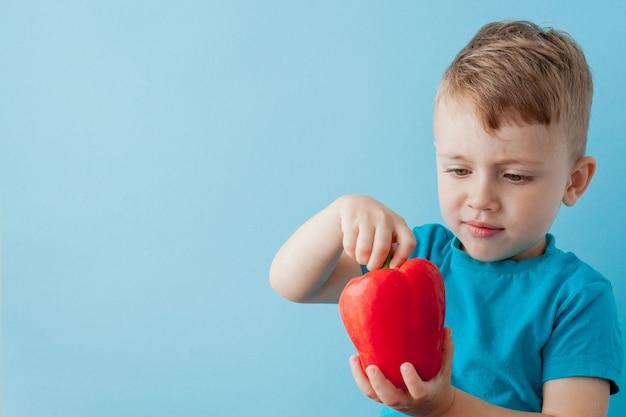 Маленький ребенок, держа перец в его руках на синем фоне. веганская и здоровая концепция