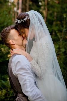 Красивые новобрачные пара прогулки в лесу. молодожены. жених и невеста держа руку в сосновом лесу, фото на день святого валентина