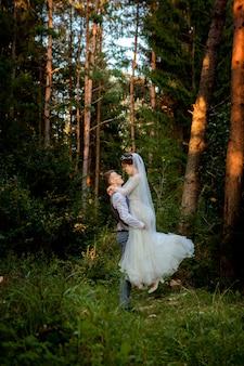 森の中を歩く美しい新婚カップル。ハネムーナー。松の森で手を握って新郎新婦、バレンタインデーの写真