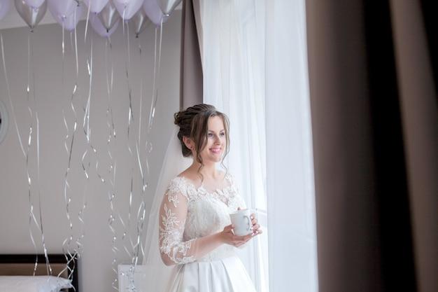 一杯のコーヒーと窓枠の近くのペニョワールランジェリーで美しい少女花嫁と新郎、花嫁の朝、結婚式の日を待っています。