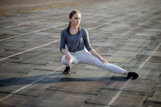 若い女性は夏にスタジアムでトレーニングします。スポーツウーマン、ストレッチ、ウォーミングアップ、屋外での運動。健康的な生活様式
