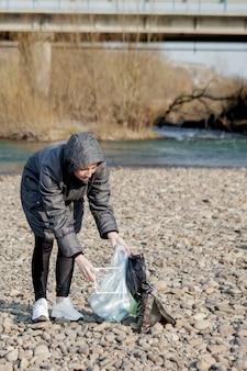 ビーチからビニール製のゴミを収集し、それをリサイクルのために黒いビニール袋に入れる若い女性。クリーニングとリサイクルのコンセプト。