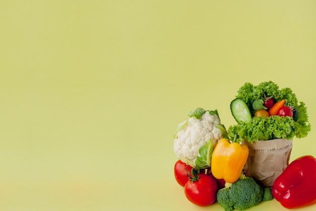 黄色の背景に茶色の紙クラフト食料品袋に有機野菜ブロッコリーきゅうりピーマンりんご。健康的な食事食物繊維ビーガンプラスチック無料のコンセプト。ポスターバナー