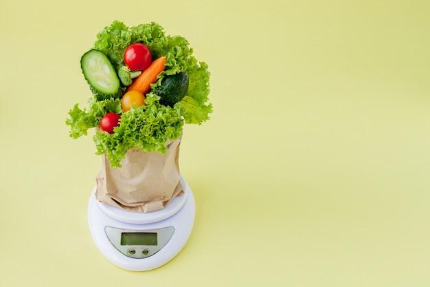 黄色の背景のスケールで新鮮な野菜。ビーガンと健康の概念。