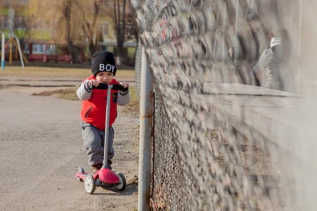 子供は屋外でスクーターに乗って、アクティブなスポーツの子供