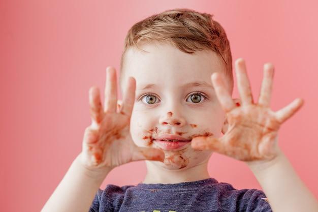 チョコレートを食べる少年。かわいい幸せな少年は彼の口の周りにチョコレートを塗った。子供の概念。