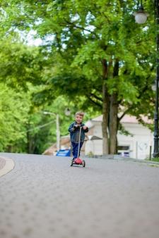 夏の都市公園で少年乗馬スクーター。子供のスポーツアウトドア。彼のスクーターで遊んで幸せな子。子供は公園でスクーターに乗ることを学びます。幸せな子供時代