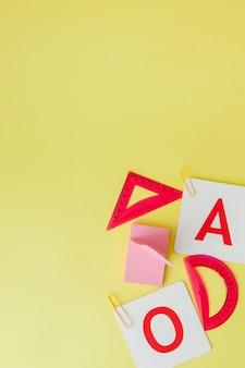 Обратно в школу концепции с пространством для текста. вид сверху. копировать пространство школьные канцтовары. творческий стол с красочными канцтовары. цветные скрепки. школьные принадлежности на желтом фоне. офисный стол