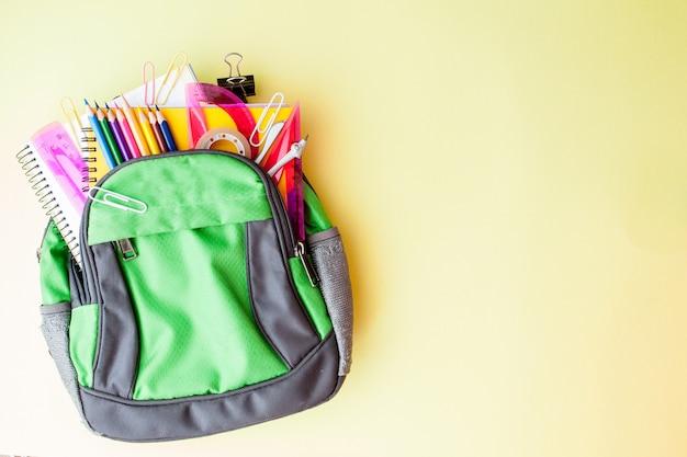 黄色の背景にバックパックと学校の文房具とフラットレイアウト構成