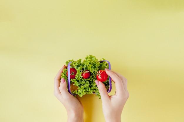 黄色の背景の上面にバスケットで新鮮な野菜を持っている手