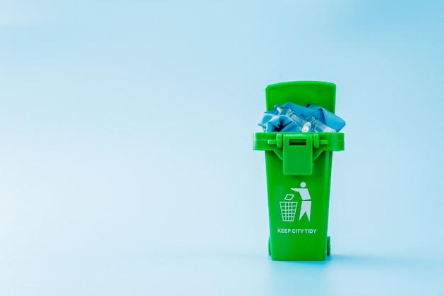 緑のゴミ、青色の背景にゴミ箱