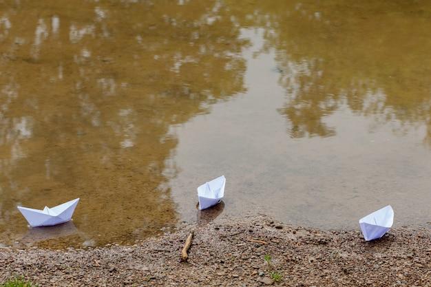 Белая бумажная игрушка лодка на голубой воде у берега