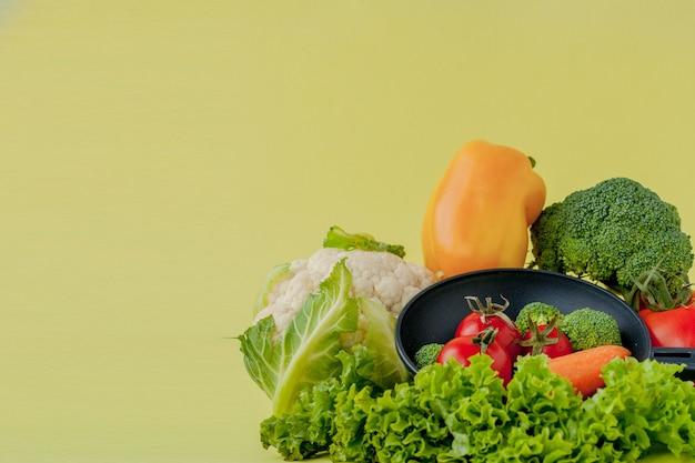 Свежие овощи на сковороде на желтом фоне. веганская и здоровая концепция