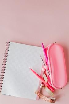 Обратно в школу. блокнот, пенал с ручкой и карандаши на розовом фоне
