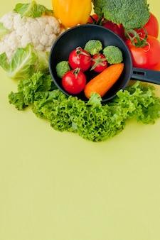 Органическая еда. полезные овощи с брокколи, салатом, красным и желтым сладким перцем, огурцом на сковороде черного цвета