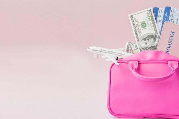 旅行者ピンクのスーツケースとパスポートドキュメント、ピンクの背景、旅と旅行のコンセプトの財布